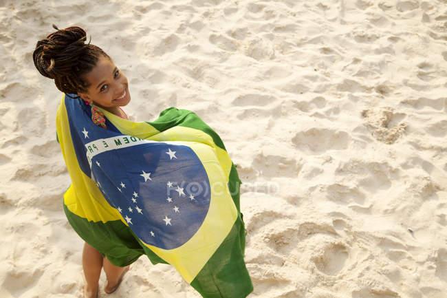 Портрет молодой женщины, завернутой в бразильский флаг, пляж Ипанема, Рио-де-Жанейро, Бразилия — стоковое фото