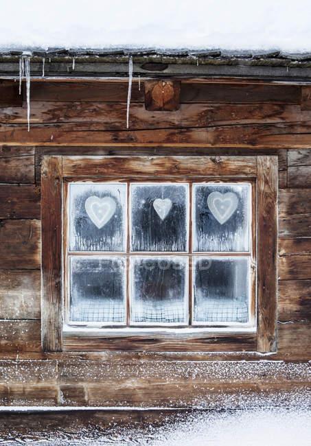 Coeurs sur la fenêtre de la cabane en rondins, Alpes autrichiennes, Autriche — Photo de stock