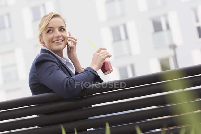 Business woman having lunch break on park bench — Stock Photo