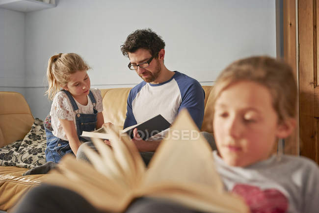 Girl, sister and father reading books in living room — Stock Photo