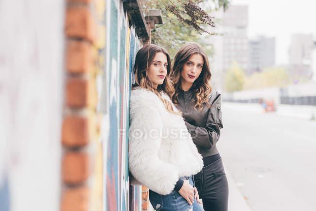 Ritratto di due sorelle gemelle, all'aperto, che si appoggia contro la parete — Foto stock