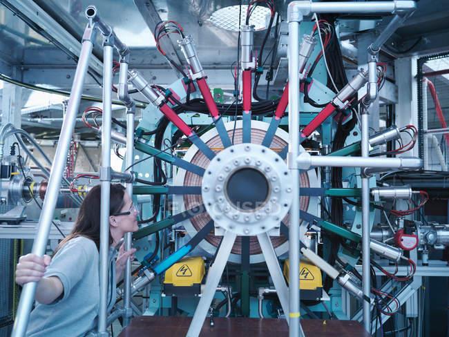 Une scientifique féminine inspecte un accélérateur de particules — Photo de stock