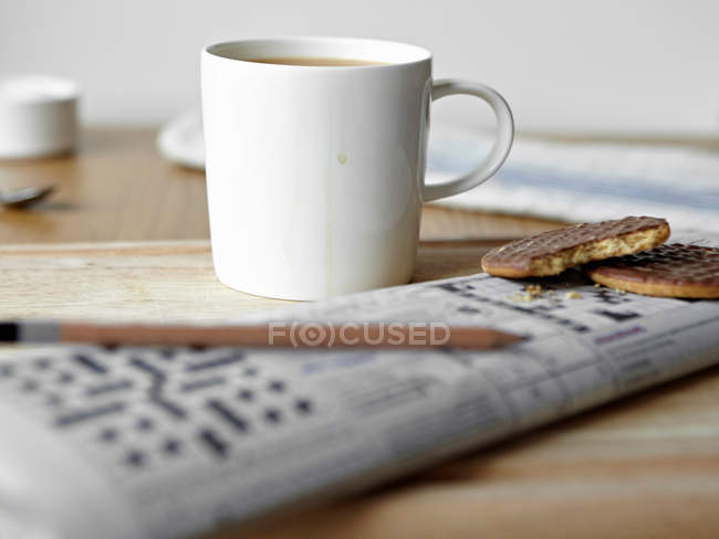 Coffee cup with cookies and crossword on table — Stock Photo