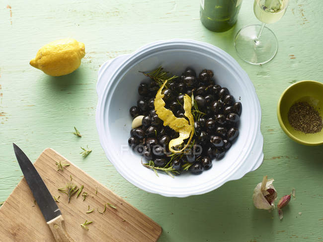 Top view of bowl of black olives with lemon peel on table — Stock Photo