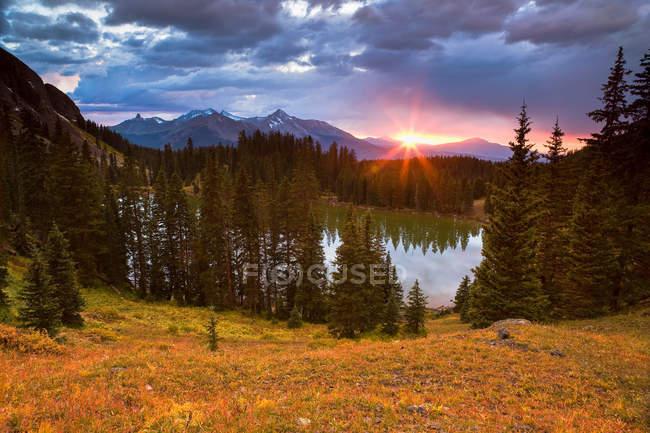 Sun setting over still rural lake — Stock Photo