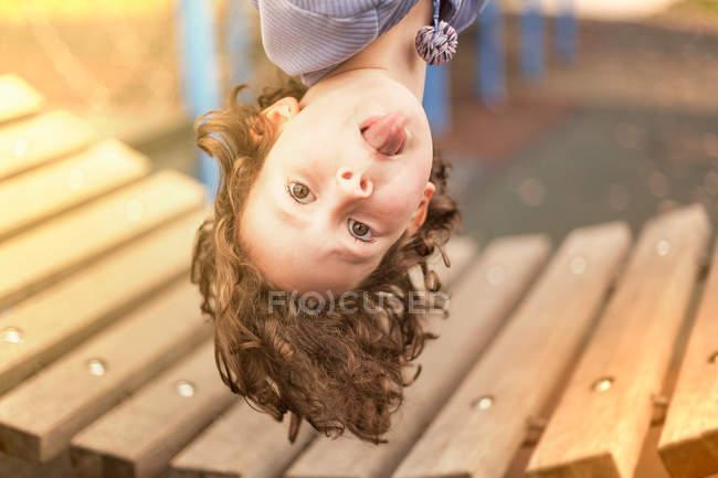 Mädchen auf Spielplatz hängt kopfüber und blickt in Kamera, die die Zunge herausstreckt — Stockfoto