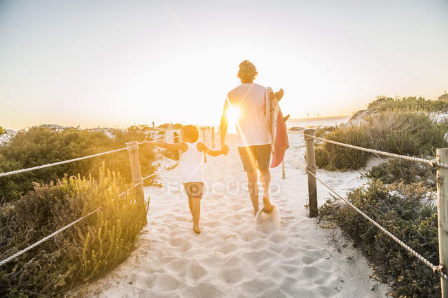 Rear view of father and son on beach holding hands, carrying surfboard — Stock Photo