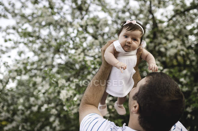 Portrait of baby girl held up by her father in garden — Stock Photo