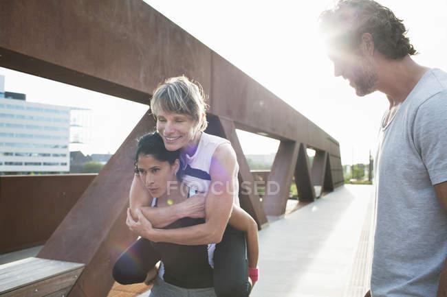 Duas mulheres dando piggyback em passarela urbana com treinador pessoal masculino — Fotografia de Stock