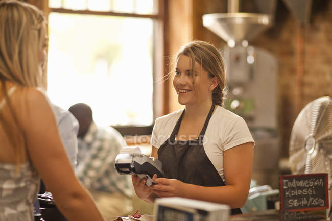 Молода жінка, яка обслуговує клієнта в кав'ярні — стокове фото