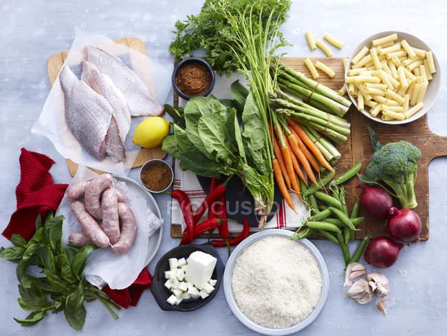 Вид сверху рыб, свиные сосиски, сыр Фета и выбор свежих органических трав и овощей — стоковое фото