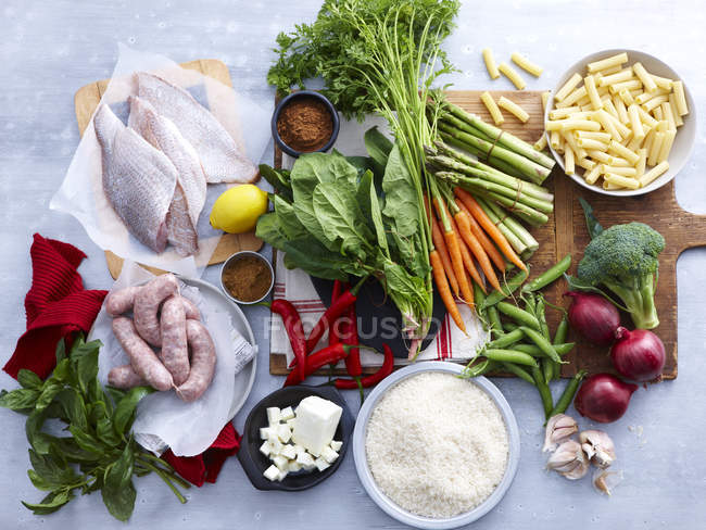 Top view of fish, pork sausages, feta and selection of fresh organic herbs and vegetables — Stock Photo