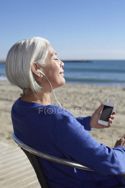 Mature woman listening to music with earbuds on beach — Stock Photo