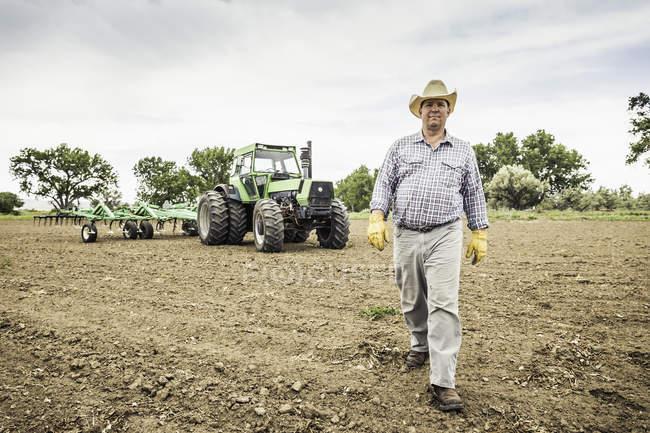 Agriculteur marche du tracteur et une charrue dans le champ — Photo de stock