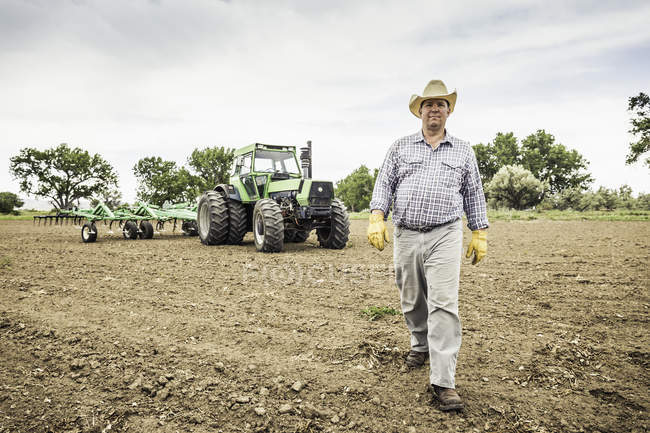 Farmer walking from tractor and plough in field — Stock Photo