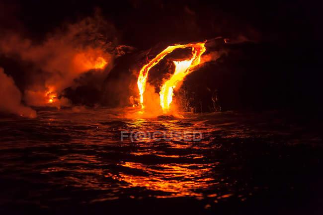 Lava flow into sea at night — Stock Photo