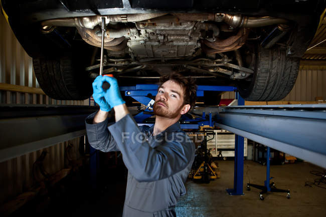 Male mechanic doing maintenance under car — Stock Photo