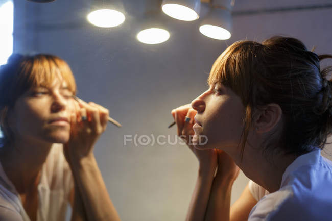 Mid adult woman applying eyeliner in bathroom mirror — Stock Photo