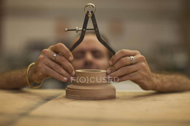 Close up of carpenter measuring turning wood in workshop — Stock Photo