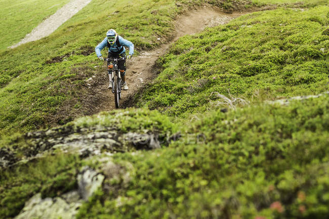 Jovem motociclista de montanha do sexo feminino pedalando pista de encosta — Fotografia de Stock