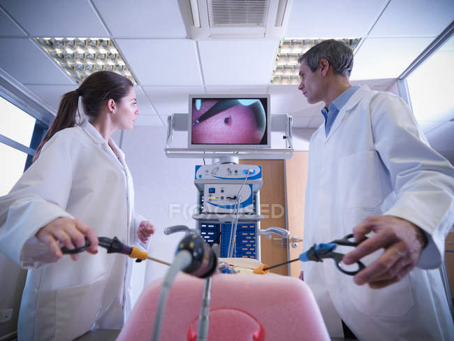 Male and female scientists use a medical simulator for training. — Stock Photo
