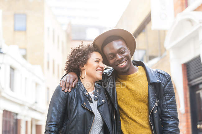 Young couple walking down street smiling — Stock Photo