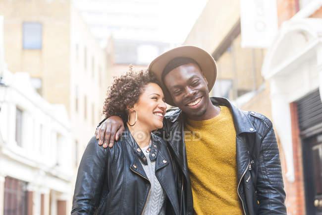 Молодая пара, идущая по улице улыбаясь — стоковое фото