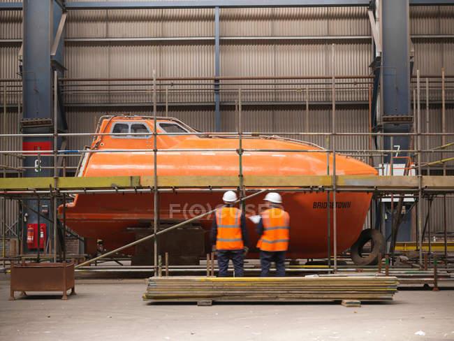 Інженери оглядають шлюпки у судноплавні — стокове фото