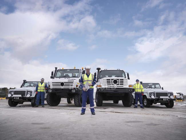 Работники группы реагирования на чрезвычайные ситуации со специальными грузовиками — стоковое фото