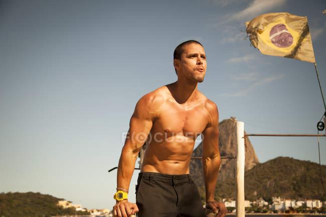 Mid adult man training on parallel bars, Rio De Janeiro, Brazil — Stock Photo