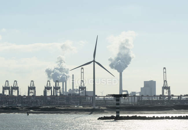 Silhouetted view of wind turbine, container terminal and coal fired power plant at Rotterdam harbour, Netherlands — Stock Photo