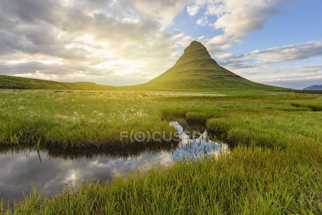 Болотистой местности с зеленого холма и пасмурное небо — стоковое фото