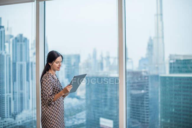 Бизнесвумен с цифровым планшетом у окна, Дубай, Объединенные Арабские Эмираты — стоковое фото