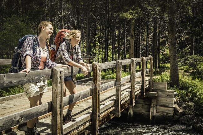 Teenager-Mädchen und jungen weiblichen Wanderer mit Blick vom Fluss Fußgängerbrücke, Red Lodge, Montana, Usa — Stockfoto