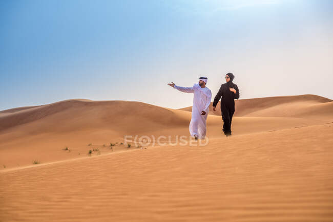 Пара одягнена в традиційний середній східний одяг, що вказує на пустельну дюну, Дубай, Об