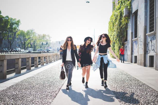 Tre giovani donne alla moda che camminano lungo il marciapiede — Foto stock