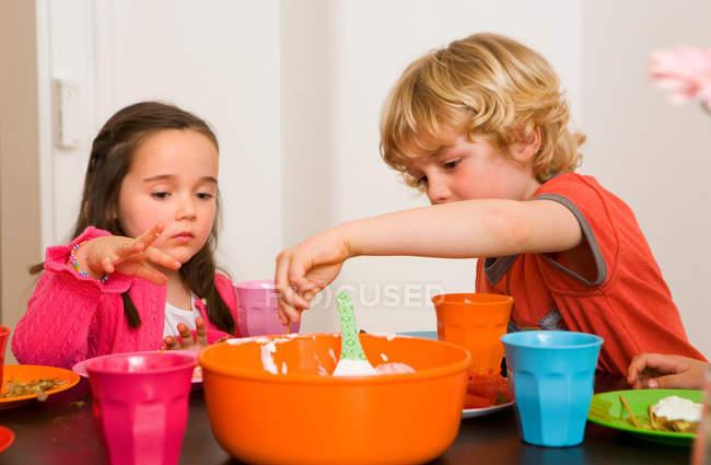 Діти зануренням овочів у соус — стокове фото