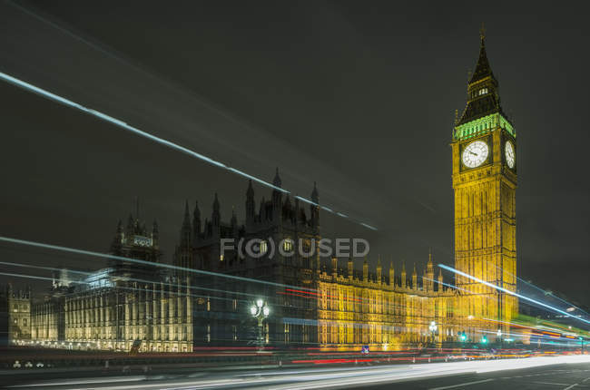 Traffic light trails passing Westminster Palace and Big Ben at night, London, UK — Stock Photo