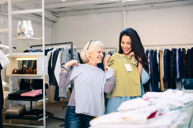 Women in clothes shop fooling around with t-shirts smiling — Stock Photo
