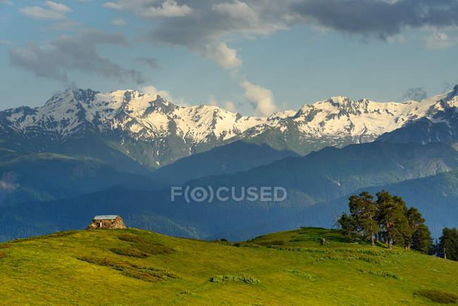 Сарай на пагорбі і далеких гір з хмарного неба — стокове фото
