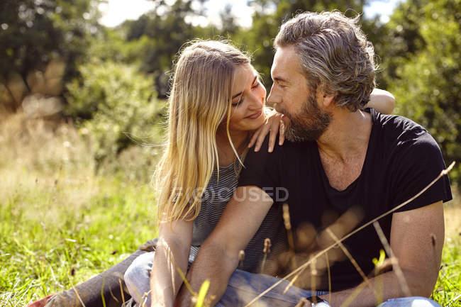 Romantisch zu zweit sitzen betrachten einander im ländlichen Bereich — Stockfoto