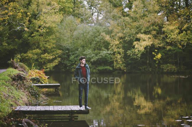 Jeune homme debout sur le bord de jetée de la rivière — Photo de stock