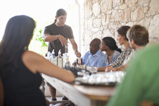 People sitting around table and tasting drinks — Stock Photo