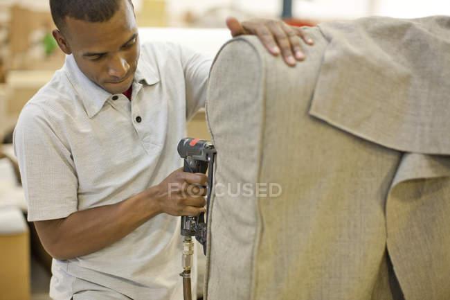 Estofador que une a matéria têxtil ao sofá usando o injetor do grampo — Fotografia de Stock