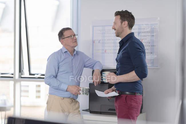 Два офисных работника говорить, стоя в офисе на принтере, человек, держащий бумажный документ — стоковое фото