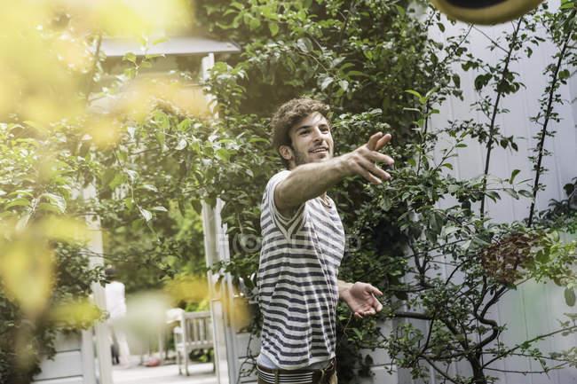 Giovane uomo che lancia palla in giardino — Foto stock