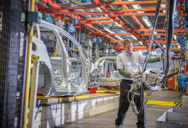 Worker with car bodies and machinery on production line in car factory — Stock Photo