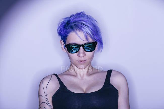 Studioportrait von lila dunkelhaarige Frau mit Sonnenbrille — Stockfoto
