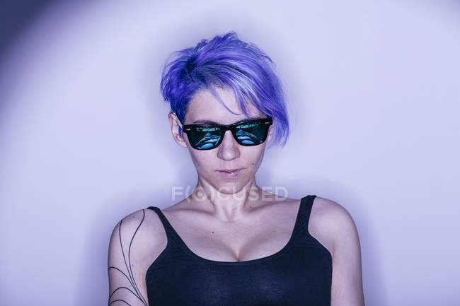 Studio portrait of purple haired woman in sunglasses — Stock Photo