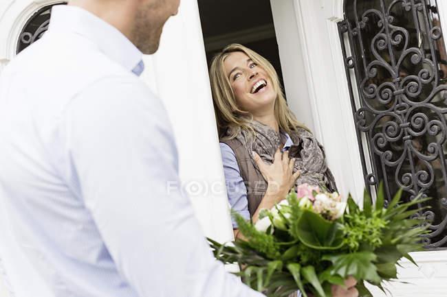 Frau öffnen Tür, Mann mit Blumenstrauß — Stockfoto